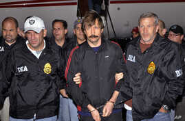 This Nov. 16, 2010, file photo, provided by the Drug Enforcement Administration (DEA), shows Russian arms trafficking suspect Viktor Bout, center, led by DEA officers off a flight From Bangkok to New York after his extradition to face terrorism charg