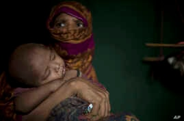 """In this June 25, 2018, photo, """"S"""" holds her baby boy as she sits in her shelter in Balukhali refugee camp in Bangladesh."""