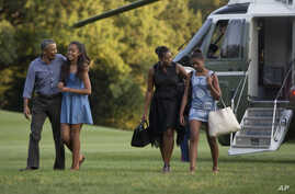 From left, President Barack Obama with daughter Malia and first lady Michelle Obama with daughter Sasha, walk form Marine One across the South Lawn of the White House in Washington, Sunday, Aug. 23, 2015.