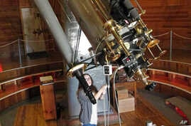FILE - Sarah Conant of the Lowell Observatory in Flagstaff, Ariz., adjusts a telescope, March 2, 2016. The state's desert sky is a haven for astronomers and other opponents of light pollution. Legislation introduced last year that would have allowed