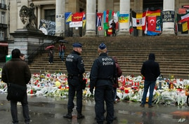 Police patrol one of the memorial sites for the victims of the recent attacks in Brussels at the Place de la Bourse in Brussels, March, 25, 2016.