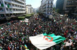 Algerians march with a giant national flag during a protest in Algiers, Algeria, March 15, 2019. Tens of thousands of people gathered Friday in Algeria's capital and other cities amid heavy security for what could be decisive protests against longtim