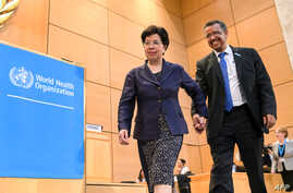 Outgoing Director General of the World Health Organization (WHO), China's Margaret Chan (L), leads new WHO Director General Ethiopia's Tedros Adhanom Ghebreyesus to the podium after his election during the World Health Assembly (WHA) in Geneva, Switz