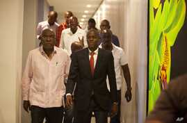 Presidential candidate Jovenel Moise, right, from the PHTK party, leaves after a press conference in Port-au-Prince, Haiti, Monday, Jan. 4, 2016.