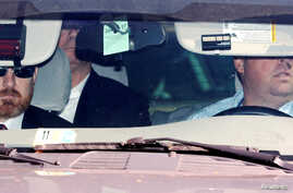 Federal agents arrive with former Trump campaign manager Paul Manafort (back seat) in custody on charges related to special counsel Robert Mueller's investigation into alleged Russian meddling in the 2016 U.S. presidential election, at the federal co