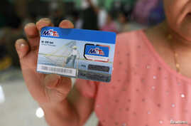 A woman holds up a SIM card, which she won in a June lottery, in Rangoon, Burma, June 24, 2013.