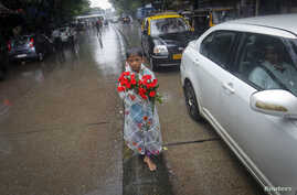 A boy sells roses while standing on a road divider during in Mumbai in this July 12, 2013, file photo.