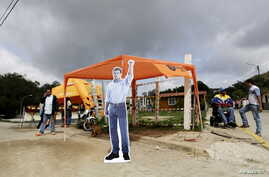 A cardboard picture of jailed Venezuelan opposition leader Leopoldo Lopez is seen next to his supporters outside the prison of Ramo Verde, on the outskirts of Caracas, June 18, 2015.