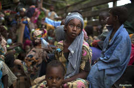 A girl sits at the back of a truck as she prepares to flee sectarian violence with other Muslim families in a convoy escorted by AU peacekeepers towards the border with Cameroon, in the town of Bouar, Central African Republic, March 9, 2014.
