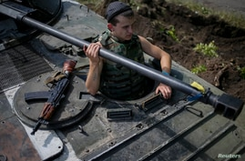 A Ukrainian soldier looks out from an armored vehicle near the eastern Ukrainian city of Konstantinovka July 10, 2014