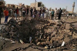 Civilians inspect a crater caused by a suicide car bombing at a busy market in Khan Bani Saad in the Diyala province, about 30 kilomters (20 miles) northeast of Baghdad, Iraq, July 18, 2015.