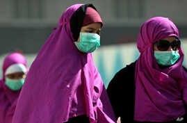 FILE - Muslim pilgrims wear surgical masks to prevent infection from respiratory virus known as the Middle East respiratory syndrome (MERS) in the holy city of Mecca, Saudi Arabia.