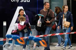 Travelers evacuate Orly airport, south of Paris, March, 18, 2017. Soldiers at Paris' busy Orly Aiport shot and killed a man who wrestled one of their colleagues to the ground and tried to steal her rifle Saturday, officials said.