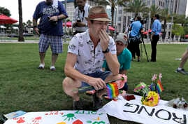 Johnathan Dalton breaks down as he places flowers on a makeshift memorial in memory of two of his friends who were killed during a fatal shooting at the Pulse Orlando nightclub in Orlando, Fla., June 13, 2016.