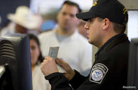 FILE - A U.S. Customs and Border Protection officer checks a passport at a border crossing in San Ysidro, California, Jan. 31, 2008.