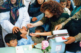 Ellyn Ogden, USAID's worldwide polio eradication coordinator, immunizes a child during a festive kick-off event for a polio vaccination campaign in Kabul, Afghanistan.