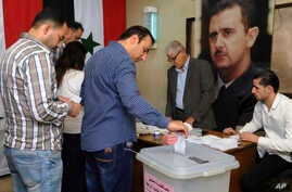 In this photo released by the Syrian official news agency SANA, Syrians cast their votes at a polling station during municipal elections in Damascus, Sept 16, 2018.