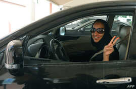 FILE - Saudi activist Manal al-Sharif flashes the sign for victory as she drives her car in Dubai, Oct. 22, 2013.