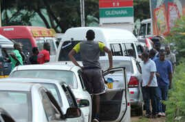Motorists wait in a fuel queue in the capital Harare, Friday, Jan. 11, 2019. Zimbabwe's president has more than doubled the price of gasoline, hoping the increase will end severe shortages that are fueling public anger.