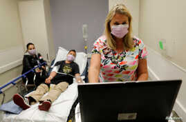 FILE - Emergency room nurse Christine Bauer treats Joshua Lagade of Vista, California, for the flu in the emergency room at Palomar Medical Center in Escondido, California, U.S., Jan.18, 2018.