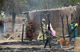 People stand near burnt structures in the aftermath of what Nigerian authorities said was heavy fighting between security forces and Islamist militants in Baga, a fishing town on the shores of Lake Chad, adjacent to the Chadian border, April 21, 2013