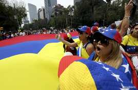 FILE - People carry a giant Venezuelan flag during a protest of Venezuelan citizens residing in Mexico, against the government of Venezuela's President Nicolas Maduro and the violence resulting from anti-government protests, in Mexico City, Feb. 23,