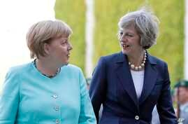 German Chancellor Angela Merkel, left, and British Prime Minister Theresa May walk on the red carpet during a military welcoming ceremony at the chancellery in Berlin Wednesday, July 20, 2016, on May's first foreign trip after being named British Pri
