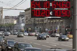 FILE - Cars drive past an exchange office sign showing the currency exchange rate in Moscow, Russia, Aug. 10, 2015.
