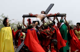 Devotees dressed as Roman soldiers lifted Ruben Enaje on the cross after he was nailed to it for his 32nd time during a re-enactment of Jesus Christ's sufferings as part of Good Friday rituals in the village of San Pedro Cutud, Pampanga province, nor