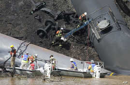 FILE – Workers remove damaged CSX tanker cars carrying cru