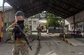 Pro-Russian armed men walk in an entrance to a border guards base, which they seized, on the outskirts of Luhansk, Ukraine, June 4, 2014.