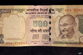This photo illustration shows a 500 rupee Indian currency note which is being withdrawn from midnight Tuesday, in New Delhi, Nov. 8, 2016.