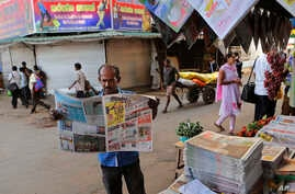A man reads a newspaper with news on a bill introduced to Parliament by Prime Minister Ranil Wickremesinghe on right to information, in Colombo, Sri Lanka, June 24, 2016.