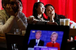 FILE - Chinese students chat as they watch a live broadcast of the presidential debate between Democratic presidential candidate Hillary Clinton and Republican presidential candidate Donald Trump, at a cafe in Beijing.