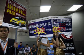 FILE - Real estate agents hold foreign properties promotion sales placards at an entrance to the China Property and Investment Show in Beijing.