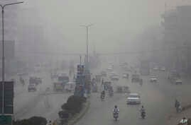 Motorcycles and vehicles are driven on a road in Peshawar, Pakistan, Nov. 5, 2017. Smog has enveloped much of Pakistan and neighboring India, causing highway accidents and respiratory problems, and forcing many residents to stay home, officials said.