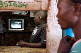 Men in a video store follow the latest provisional electoral results on the television, in Kibagare slum in Nairobi, Kenya, March 8, 2013.