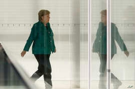 FILE - German Chancellor Angela Merkel walks through a corridor of the Reichstag building during a Christian Union parties faction meeting in Berlin, Sept. 25, 2018.