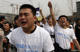 Family members of passengers of Malaysia Airlines flight MH370 cry as they shout slogans during a protest in front of the Malaysian embassy in Beijing March 25, 2014.
