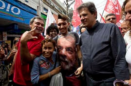 Workers' Party candidate for vice-president Fernando Haddad, 2nd from right, walks with a supporter who wears a shirt with a photo of former President Luiz Inacio Lula da Silva during a campaign rally in  Rio de Janeiro, Brazil,  Aug. 28, 2018.