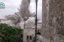 This image made from amateur video posted by Shaam News Network (SNN), an anti-Bashar Assad activist group, which has been verified and is consistent with other AP reporting, shows an explosion that destroyed the Carlton Hotel in Aleppo, Syria, Thurs