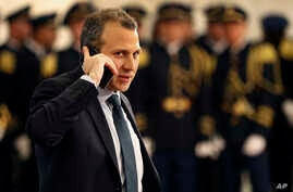 Lebanese Foreign Minister, Gibran Bassil, who is Lebanese president Michel Aoun's son-in-law and heads his Free Patriotic Movement party, speaks on his mobile phone on his arrival to the Lebanese presidential palace, in Baabda, east of Beirut, north