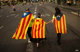 Family members wearing estelada, or independence flags, on their backs walk at the end of a big rally during the Catalan National Day in Barcelona, Spain, Sept. 11, 2017.