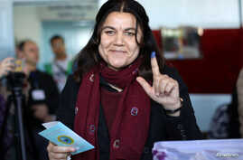 Fawza Youssef, a senior Kurdish politician, shows her ink-stained finger after casting her ballot in Qamishli, Syria, Dec. 1, 2017.