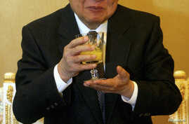 Then Cambodian King Norodom Sihanouk holds a glass during a meeting with Chinese State Councilor Dai Bingguo (not seen) in Beijing, October 30, 2006.