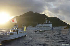 Chinese marine surveillance ship Haijian No. 51 (C) sails near Japan Coast Guard vessels (R and L) and a Japanese fishing boat (front 2nd L) as Uotsuri island, one of the disputed islands, called Senkaku in Japan and Diaoyu in China, is in background