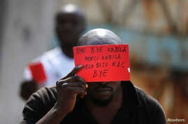 A Congolese opposition party supporter displays a red card against President Joseph Kabila in Kinshasa, Democratic Republic of Congo Dec. 19, 2016.