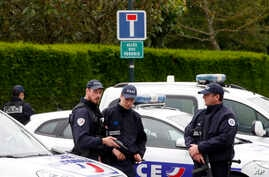 French police officers block the road leading to a crime scene the day after a knife-wielding attacker stabbed a senior police officer to death Monday evening outside his home in Magnanville, west of Paris, June 14, 2016.