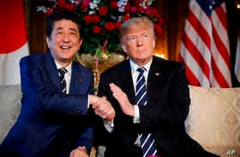 President Donald Trump and Japanese Prime Minister Shinzo Abe speak during a meeting at Trump's private Mar-a-Lago club, in Palm Beach, Fla.