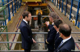 French President Emmanuel Macron (L) listens to explanations in front of a nuclear submarine as part of his visit to the Ile Longue Defence unit, submarine navy base, in Crozon, near Brest, western France, July 4, 2017.